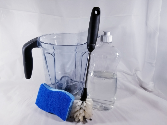 The blender container, a bottle of soap, a sponge, and a scrub brush