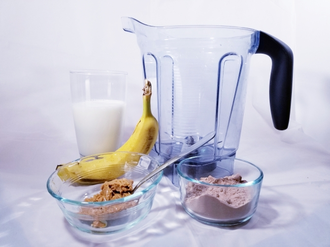 picture of the ingredients used in this recipe. Milk, a banana, peanut butter, protein powder, and the blender container.