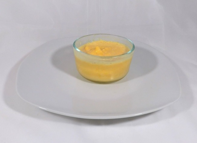orange ice cream in a bowl on a plate