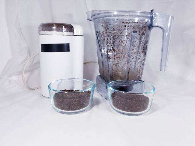 Photo of a coffee grinder, a blender container, and two containers of ground coffee